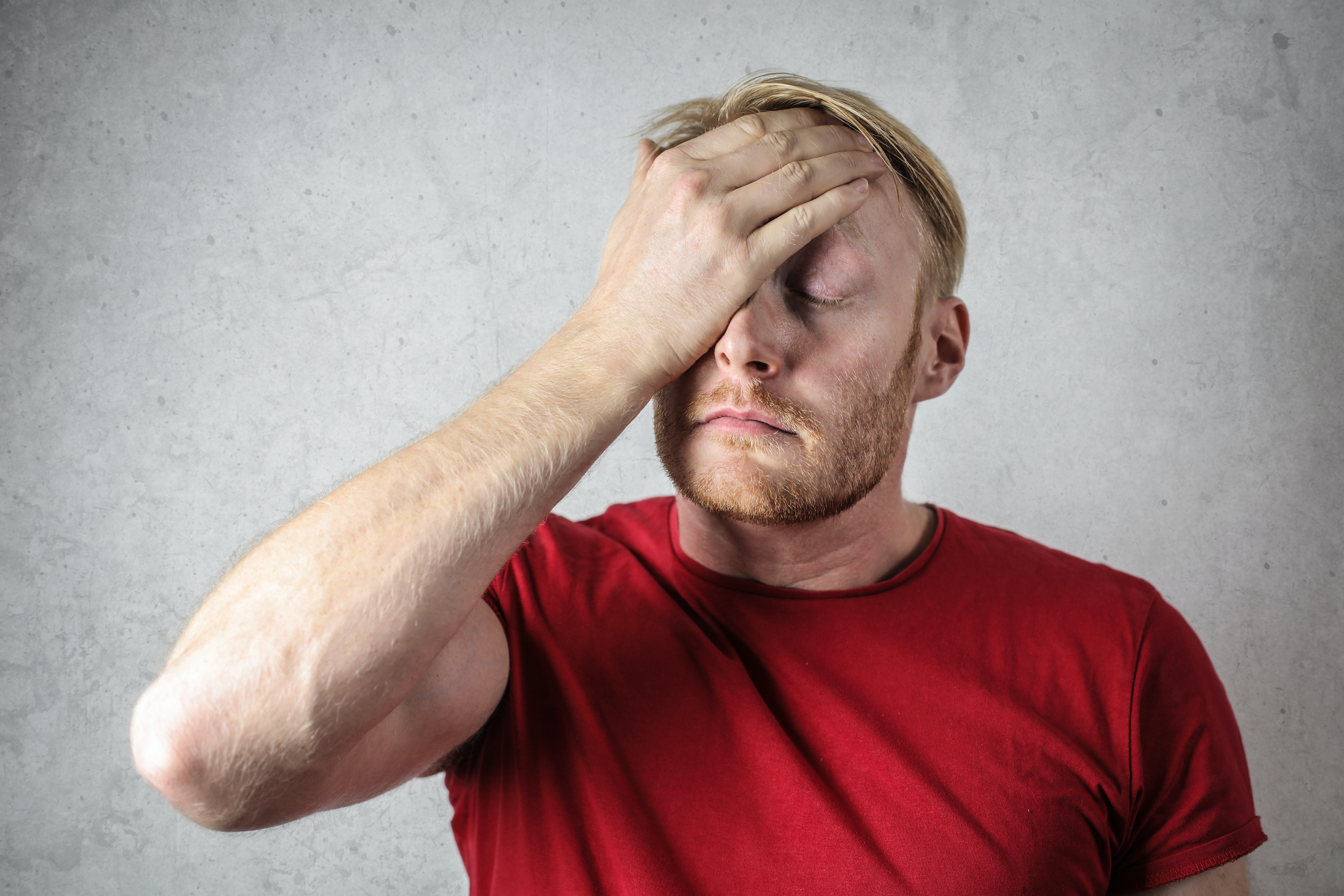 a-man-in-red-shirt-covering-his-face-3760043